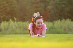 Fitness Asian Chinese woman have a rest at grass in a park. Asian Chinese woman in red sports suit,at outdoor, on grass,  inner peace, healthy life, do Royalty Free Stock Images