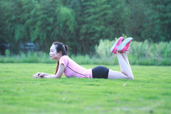 Fitness Asian Chinese woman have a rest at grass in a park. Asian Chinese woman in red sports suit,at outdoor, on grass,  inner peace, healthy life, do Royalty Free Stock Photo