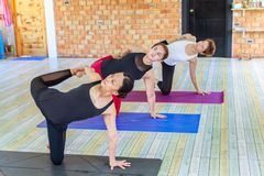 Fitness asian female group doing namaste yoga pose in row at the yoga class royalty free stock images