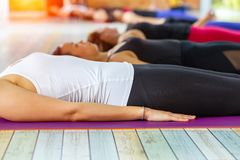 Fitness asian female group doing practicing in a yoga studio royalty free stock photography