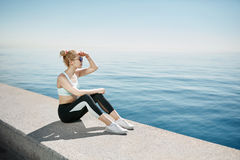 Fitness asian woman runner relaxing after city running. And working out outdoors. Young fit сhinese girl looking and enjoying view of deep sea royalty free stock image