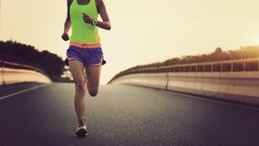 Fitness asian woman runner running on city road stock images