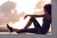 Fitness athlete runner woman relaxing in sunset. Fitness athlete sports woman relaxing after workout sitting on window looking at sunset view. Silhouette of royalty free stock image