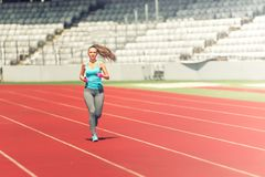 Fitness athlete running on professional track, preparing for marathon, race or olympics Royalty Free Stock Photo