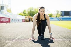 Fitness athlete on starting near stadium track preparing for a sprint. Fitness, healthy lifestyle concept. Fitness athlete on starting near stadium track royalty free stock photo