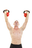 Fitness athletic man holding and lifting high up red kettlebells Royalty Free Stock Photos