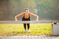 Fitness. Athletic woman standing in plank position outdoors at sunset. Concept of sport, recreation and motivation stock image