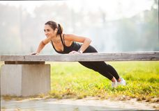 Fitness. Athletic woman standing in plank position outdoors at sunset. Concept of sport, recreation and motivation stock photography