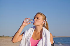 Fitness athletic young woman on beach drinking water. After exercise Stock Photo