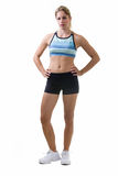 Fitness attire. Full body of an attractive blond woman in great physical shape wearing black shorts and workout top standing on white with hands on hips Stock Photo