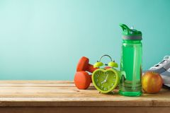 Fitness background with bottle of water, dumbbells and alarm clock stock photo