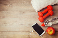 Fitness background with bottle of water, dumbbells and smartphone. View from above royalty free stock image
