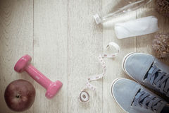 Fitness background with bottle of water, dumbbells and sneakers. Stock Photo