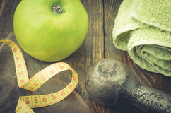 Fitness background with centimeter, apple a towel and a dumbbell. Fitness concept with centimeter, apple a towel and a dumbbell Stock Photography