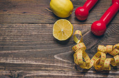 Fitness background with dumbbells, centimeter, lemon. Fitness concept with dumbbells, centimeter, lemon Stock Images