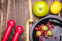 Fitness background with dumbbells, lemon, grapes, apple, pomegranate and centimeter. Fitness concept with dumbbells, lemon, grapes, apple, pomegranate and Stock Image