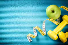 Fitness background with dumbbells, measuring tape and apple. Hea Royalty Free Stock Photo