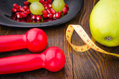 Fitness background with dumbbells, pomegranate, grapes, apple and centimeter. Fitness concept with dumbbells, pomegranate, grapes, apple, centimeter Royalty Free Stock Photos
