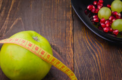 Fitness background with pomegranate, grapes, apple, centimeter. Fitness concept with pomegranate, grapes, apple, centimeter Stock Photography