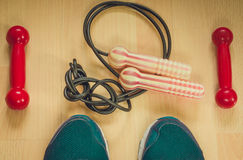 Fitness background with red dumbbells, skipping rope and athletic shoes. View from above. Fitness background with dumbbells, skipping rope and athletic shoes Stock Images