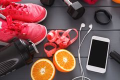 Fitness background, sport equipment, closeup. Dumbbells, grapefruit, sneakers, bottle, measuring tape and blank smartphone on grey background Royalty Free Stock Photos