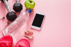 Fitness background, sport equipment, copy space. Dumbbells, bottle, apple, sneakers, measuring tape and blank smartphone on pink backdrop Stock Images