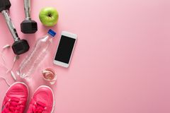 Fitness background, sport equipment, copy space. Dumbbells, bottle, apple, sneakers, measuring tape and blank smartphone on pink background Stock Photos