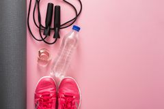 Fitness background, sport equipment, copy space. Jumping rope, bottle, sneakers, mat and measuring tape on pink background Stock Photography