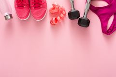 Fitness background, sport equipment, copy space. Fitness background, sport equipment, top view. Dumbbells, sneakers, shirt, measuring tape and bottle on pink Royalty Free Stock Photos