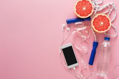 Fitness background, sport equipment, copy space. Jumping rope, bottle, grapefruit and blank smartphone on pink background Stock Photos