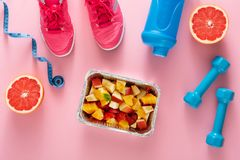 Fitness background, sport equipment, healthy food. Dumbbells, grapefruit, sneakers, bottle, measuring tape and fruit salad on pink background Royalty Free Stock Photos