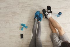 Unrecognizable fitness couple having rest at gym. Fitness background. Top view on male and female legs in sports wear, plastic bottle, dumbbells and smartphone royalty free stock photos