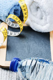 Fitness background with water bottle and towels Stock Photos