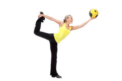 Fitness with ball: young woman doing exercises. Fitness with med ball: beautiful young woman doing exercises with ball. Yellow and black color Royalty Free Stock Image