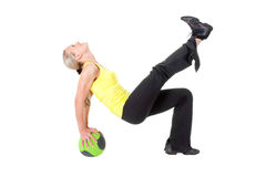Fitness with ball: young woman doing exercises. Fitness with med ball: beautiful young woman doing exercises with ball . Yellow, green and black colors Royalty Free Stock Photography