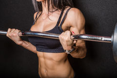 Female bodybuilder. Body of a muscular female bodybuilder lifting a barbell with a black background stock image