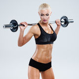 Fitness with barbell. Athletic woman pumping up muscles with barbell on gray background royalty free stock image