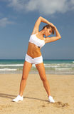 Fitness on beach. Young beautiful woman during fitness on sea beach Royalty Free Stock Image
