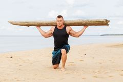 Fitness on the beach. Sport, fitness. Bodybuilder with a big wood on the beach Royalty Free Stock Image