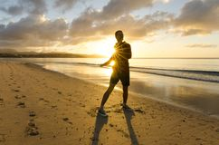 Fitness on the beach at sunrise. A man exercising on the beach at sunrise with yellow and orange colours of the sun and sun rays behind his back Stock Photo