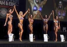 Fitness Beauties Line Up In Vancouver. The top 5 Pro Fitness Contestants raise linked arms in victory at the close of their competition at the 2015 IFBB stock photography