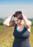 Fitness beautiful plus size woman with pain in her head. Outdoor Stock Photography