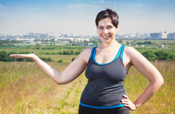 Fitness beautiful plus size woman showing something on her hand Stock Images