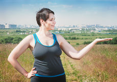 Fitness beautiful plus size woman showing something on her hand Royalty Free Stock Image