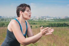 Fitness beautiful plus size woman stretching hands to something Stock Images