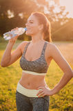 Fitness beautiful woman drinking water and sweating after exerci Stock Photography