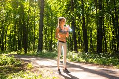 Fitness beautiful woman drinking water and sweating after exercising on summer hot day in park. Female athlete after. Work out Royalty Free Stock Photo