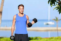 Fitness bicep curl - weight training man outdoors. Working out arms lifting dumbbells doing biceps curls. Male sports model exercising outside as part of Royalty Free Stock Photos