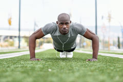 Fitness black man exercising push ups in urban background Stock Photography
