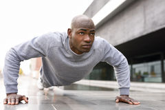 Fitness black man exercising push ups in urban background. Fitness black man exercising push ups. Male model cross-training in urban background  African guy in Stock Images